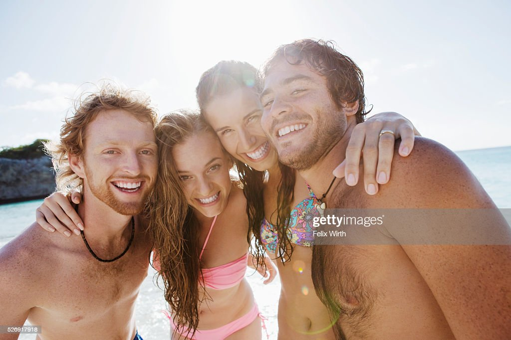 Group of friends posing together on sandy beach : Stock Photo