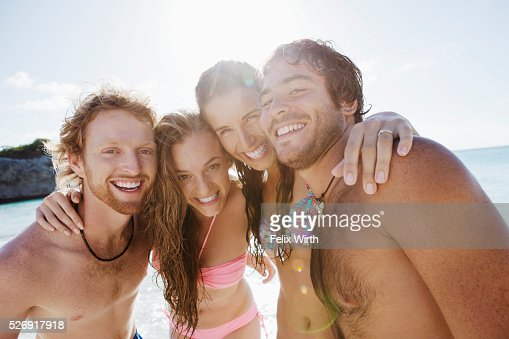Group of friends posing together on sandy beach : Stock-Foto