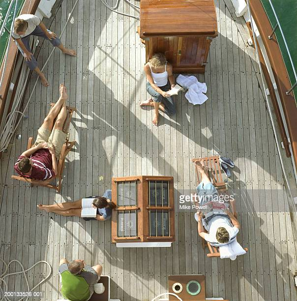 Group of friends reading on deck of sailboat, overhead view