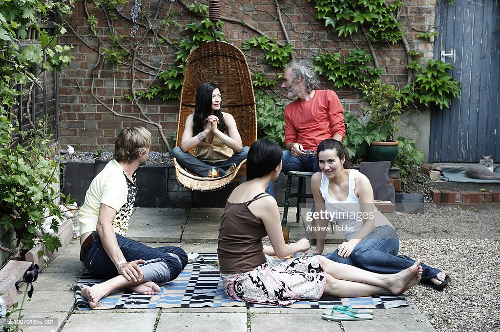 Group of friends relaxing in courtyard : Stock Photo