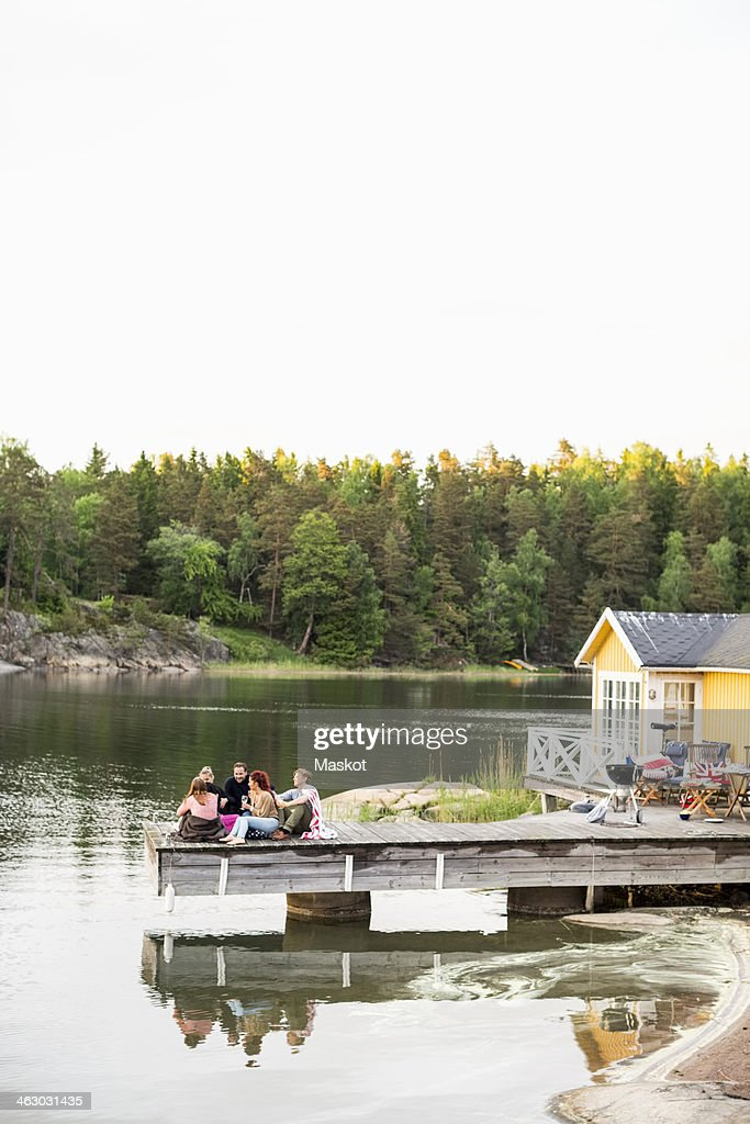 Group of friends relaxing on pier at summer house
