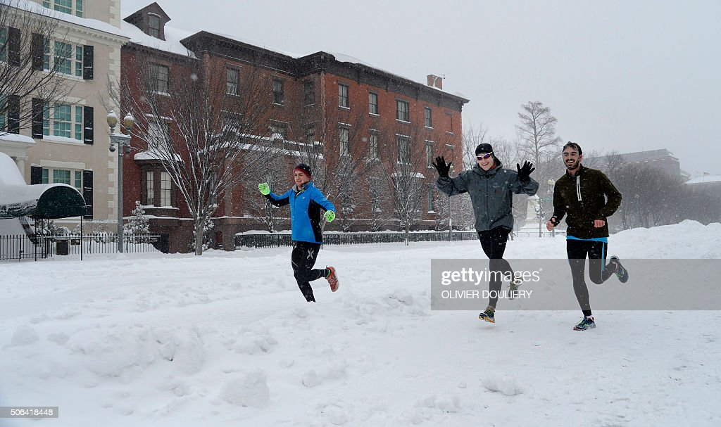 A group of friends run on Pensylvania avenue during the snow storm January 23 2016 in Washington A deadly blizzard with bonechilling winds and...