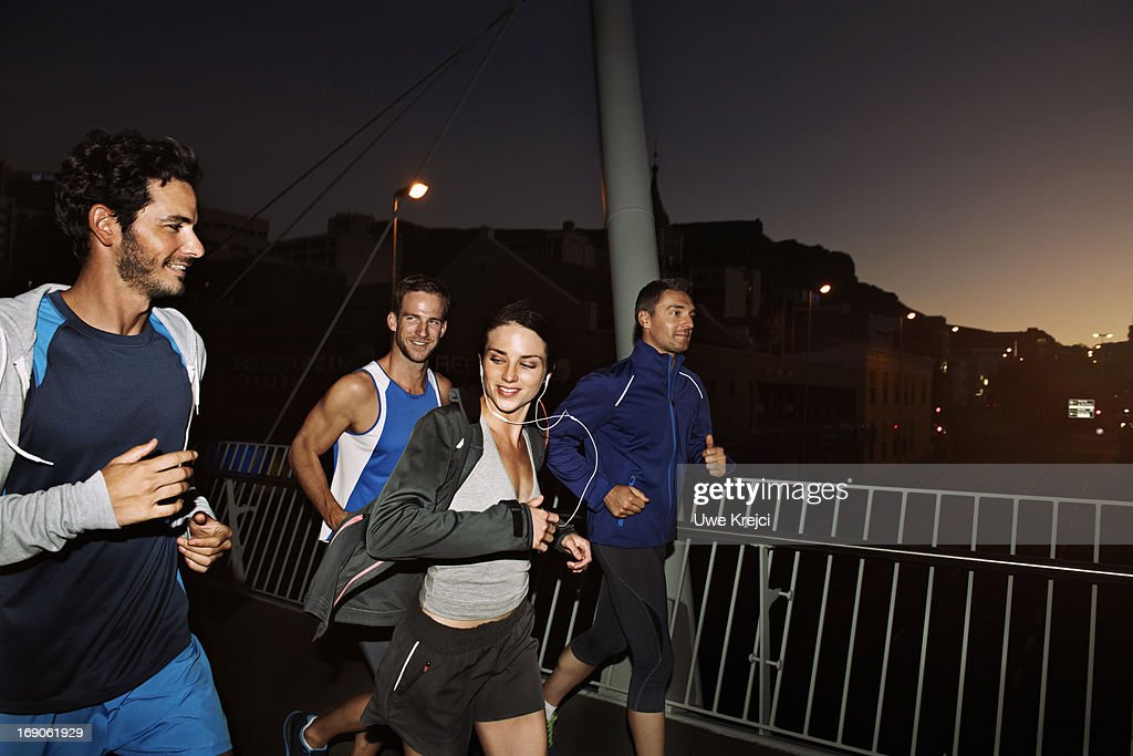 Group of friends running at night : Stock Photo