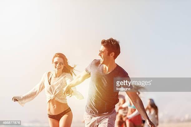Grupo de amigos corriendo en la playa
