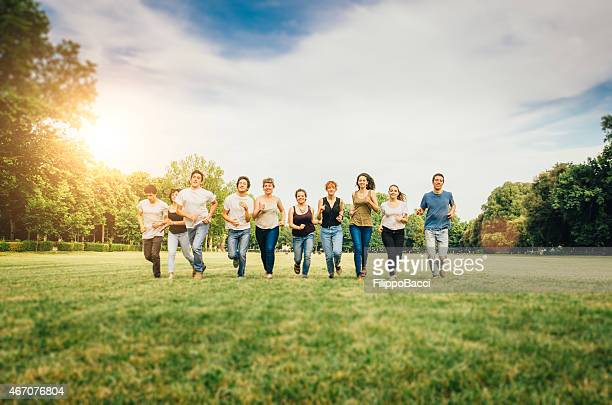 Group of friends running in a sunny park