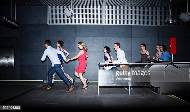 Group of friends running in subway station