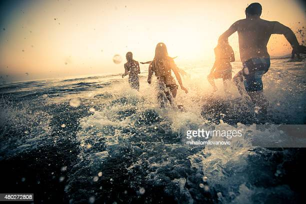 Group of friends running into the water
