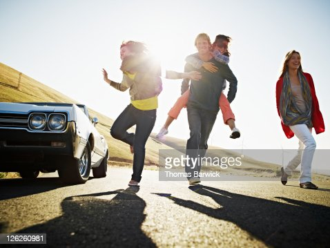 Group of friends running on empty road : Stock Photo