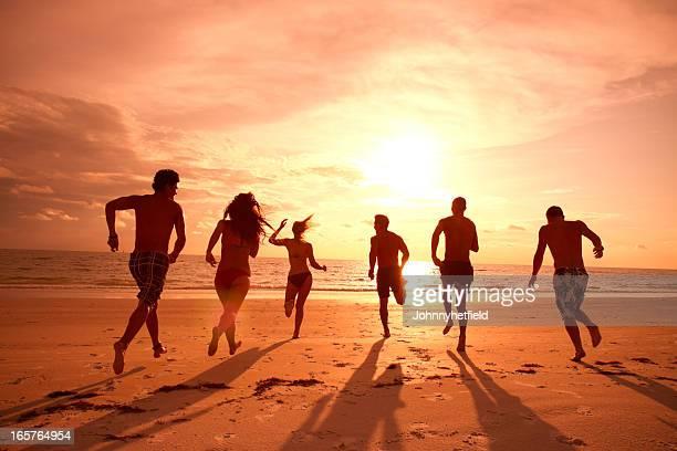 Grupo de amigos, correr na praia ao pôr do sol