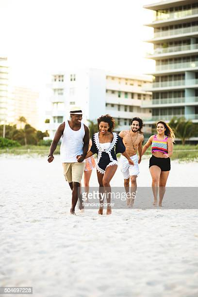 Group of friends running on the beach of miami beach