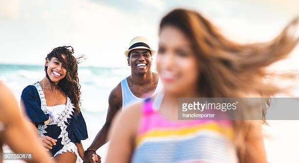 Groupe d'amis courir sur la plage de miami beach