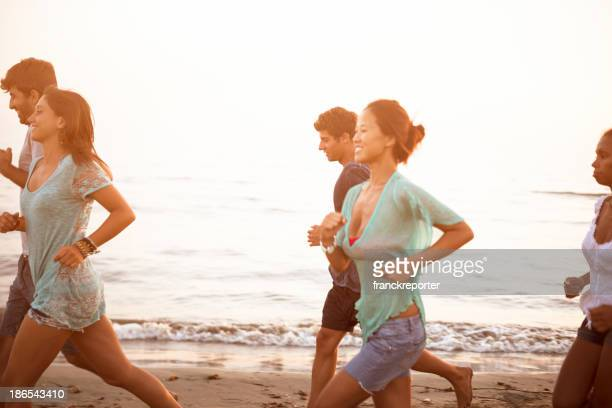 Group of friends running on the beach