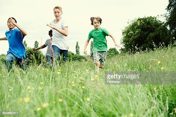 Group of friends running through a field