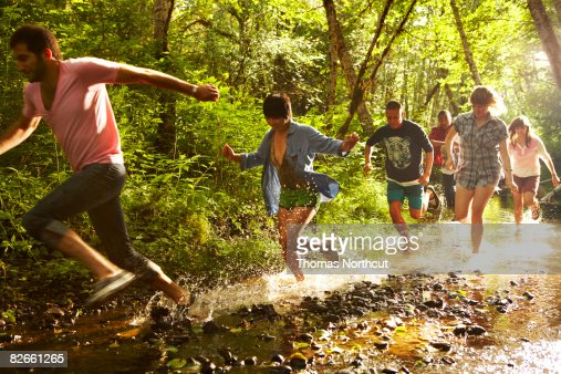 Group of friends running through stream : Stock Photo