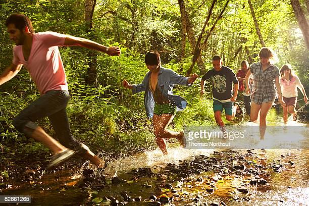 Group of friends running through stream
