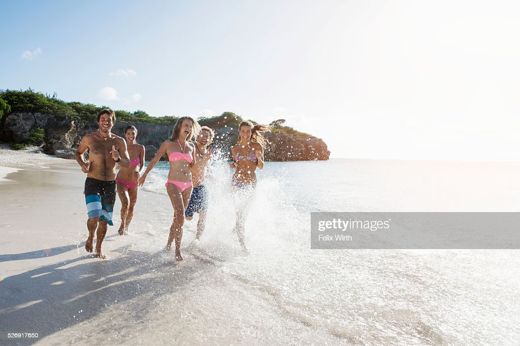 Group of friends running together along sandy beach : ストックフォト