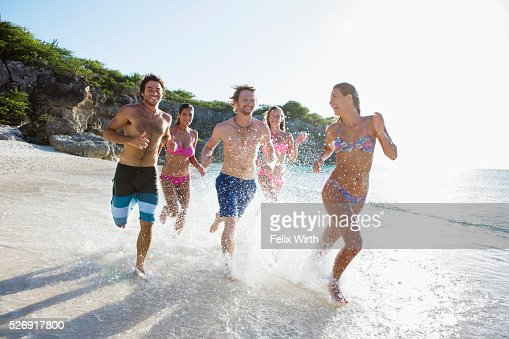 Group of friends running together along sandy beach : Foto de stock