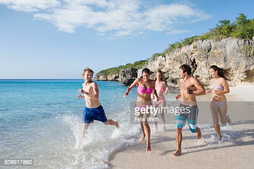 Group of friends running together along sandy beach : Stock-Foto