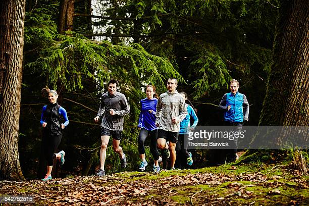 Group of friends running together on trail in park