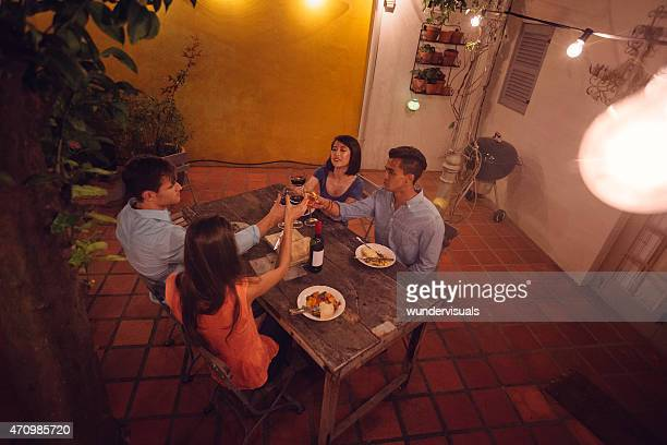 Group of friends saying cheers with wine at dinner party