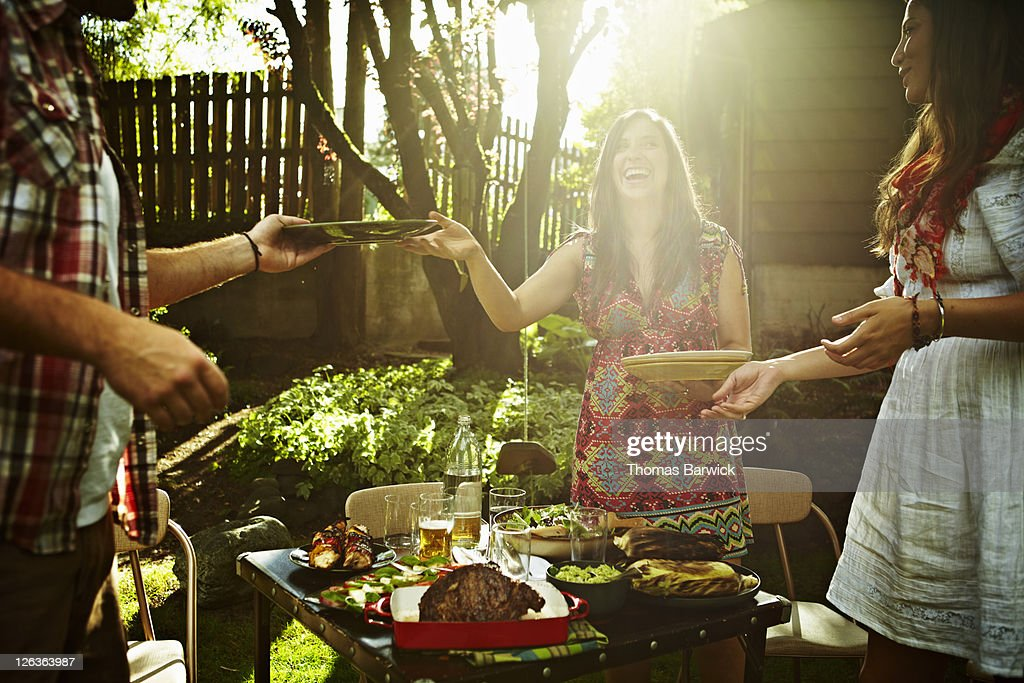Group of friends serving food at table in backyard : Stock Photo