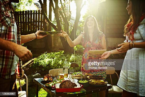 Group of friends serving food at table in backyard