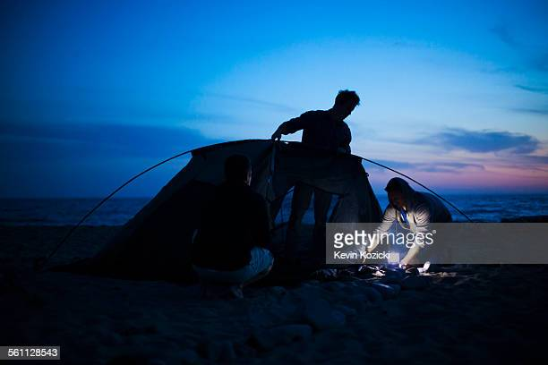 Group of friends setting up tent on beach at sunset