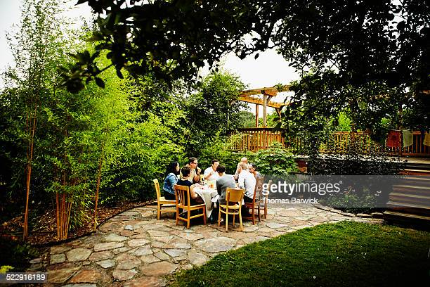 Group of friends sharing a meal at table on patio
