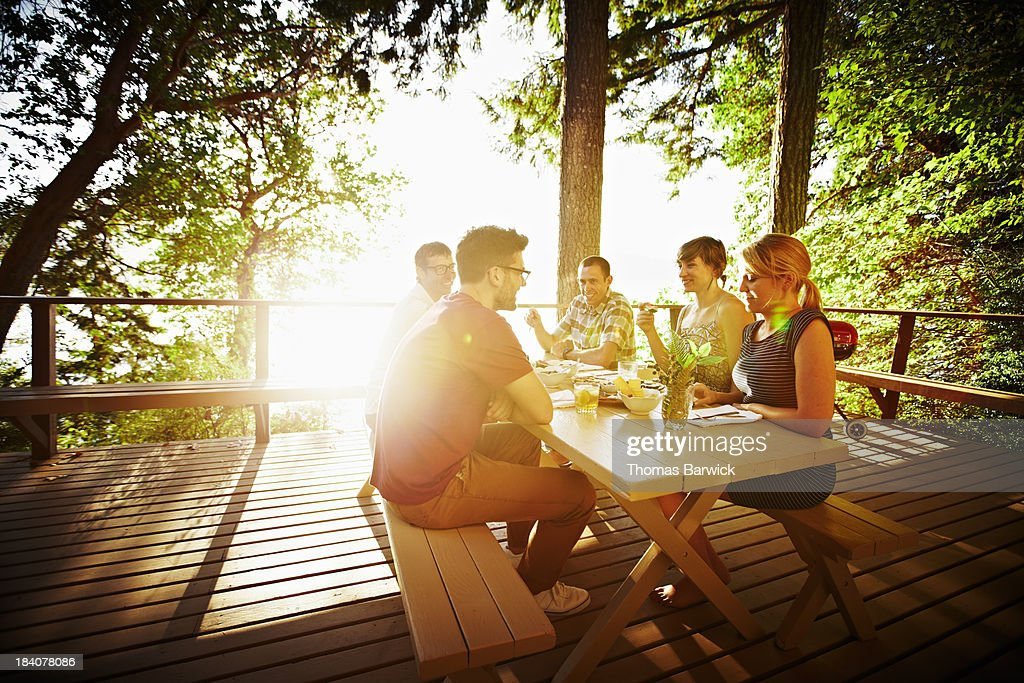 Group of friends sharing a meal on deck at sunset : Stock Photo