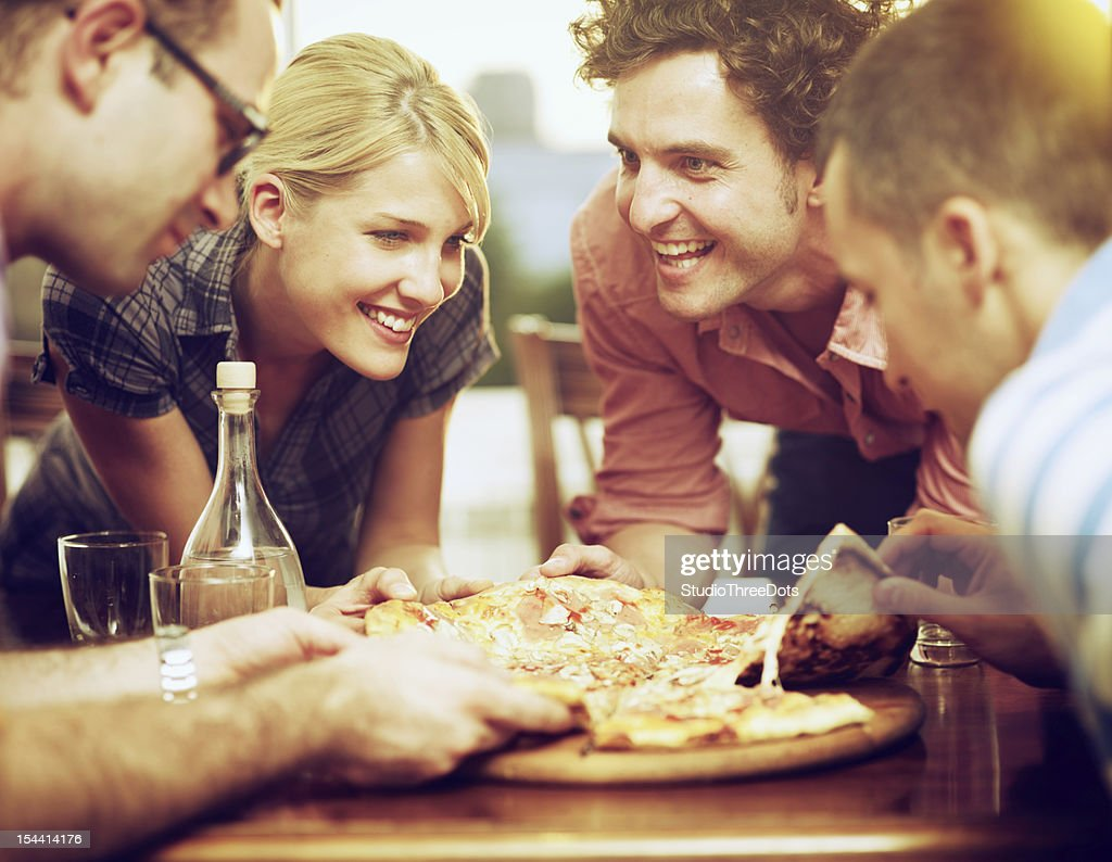 group of friends sharing a pizza : Stock Photo