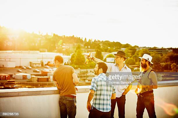 Group of friends sharing beers on rooftop