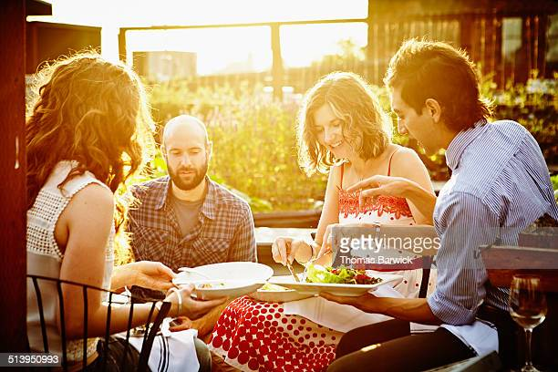 Group of friends sharing dinner at sunset