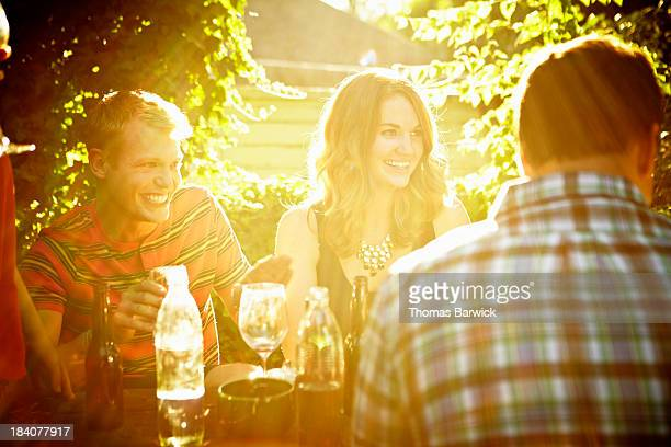 Group of friends sharing drinks in backyard