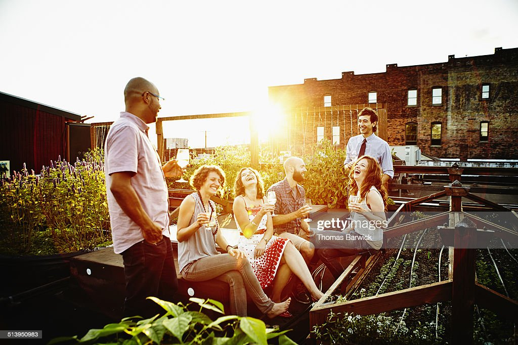 Group of friends sharing drinks on summer evening : Stock Photo
