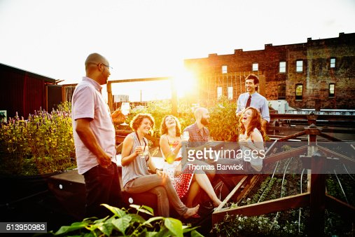 Group of friends sharing drinks on summer evening