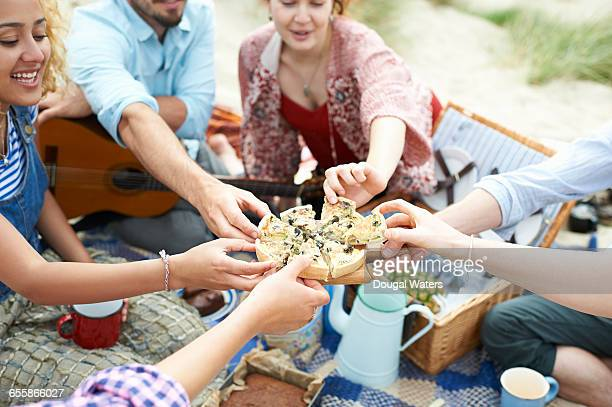 Group of friends sharing food at beach picnic.