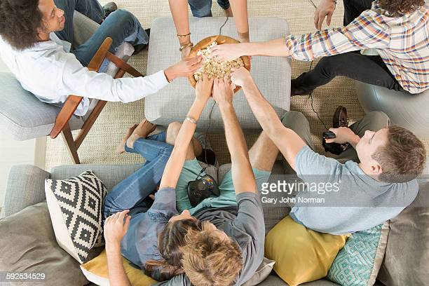 Group of friends sharing popcorn.