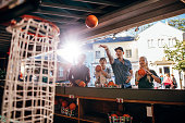 Group of friends shooting hoops at the fair. Young people playing basketball game at amusement park.