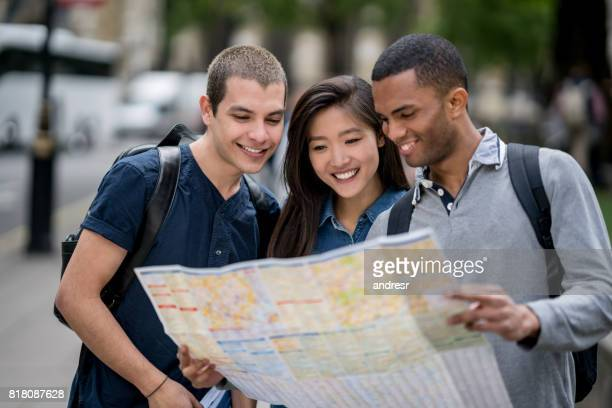 Group of friends sightseeing in London and holding a map