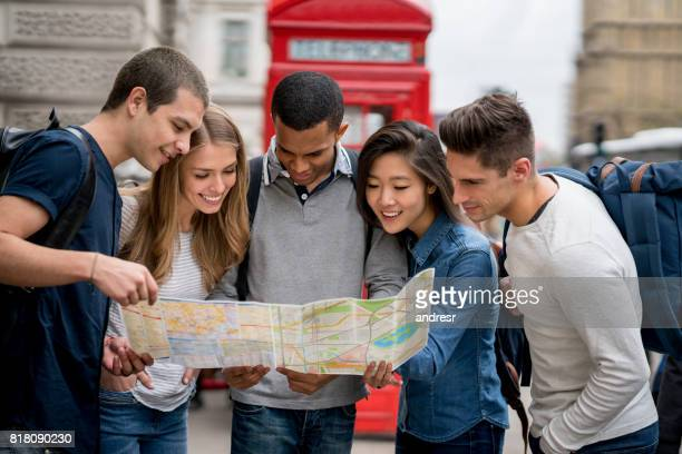 Group of friends sightseeing in London and looking at a map