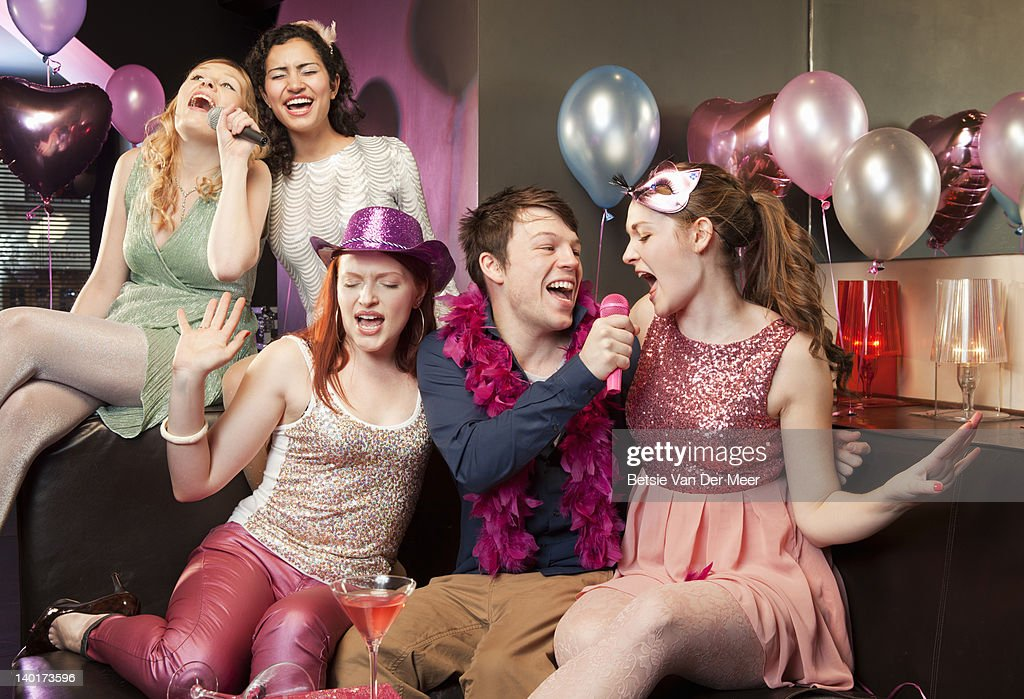 Group of friends singing karaoke. : Stock Photo