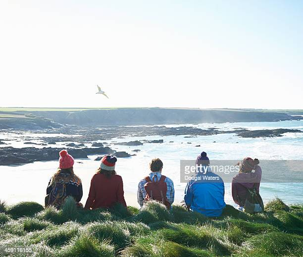 Group of friends sit on Atlantic coast.