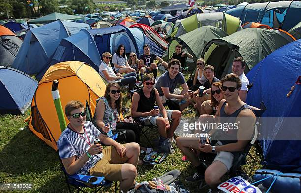 A group of friends sit with the recently erected tents at the Glastonbury Festival of Contemporary Performing Arts site at Worthy Farm Pilton on June...