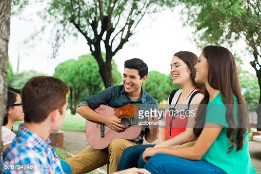 Group of friends sitting and listening to the guitar