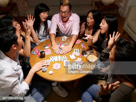 Group Of Friends Sitting Around Table In Living Room Playing Cards