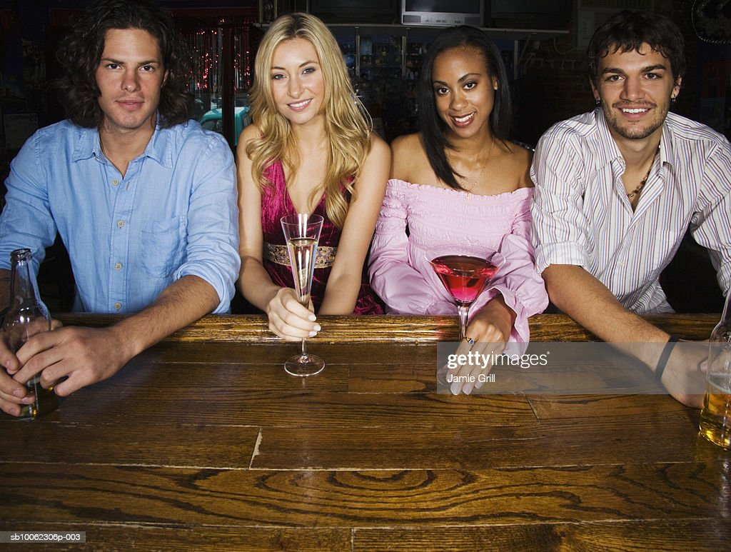 Group of friends sitting at bar area, smiling, portrait : Stock Photo