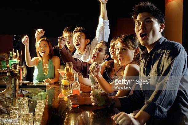 Group of friends sitting at bar, watching something