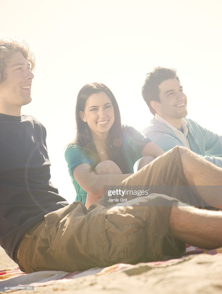 Group of friends sitting at beach : Stock Photo