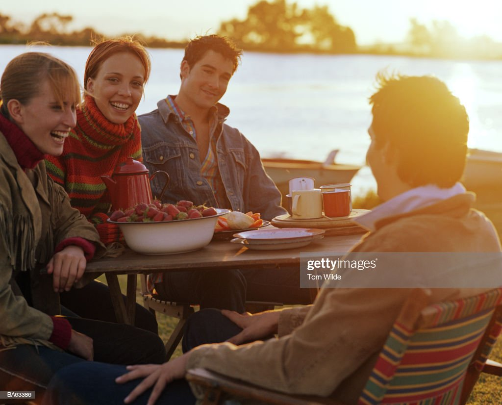 Group of friends sitting at table together, smiling, outdoors : Stock Photo