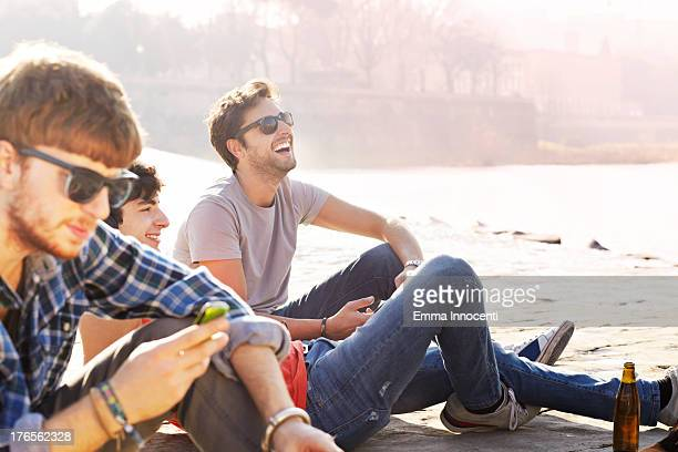 Group of friends, sitting by river, beer, phone